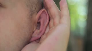 A deaf person putting his hand to his ear