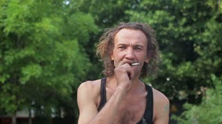 A drunk homeless man smoking gesticulating and looking at the camera