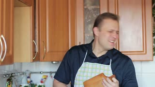 A funny guy singing and playing on a cutting board while cooking food in the kitchen, close-up