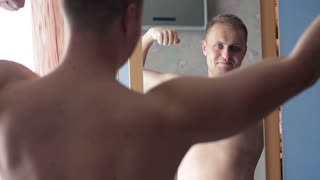 A guy in a good mood naked and looking in the mirror at himself. The concept of narcissism