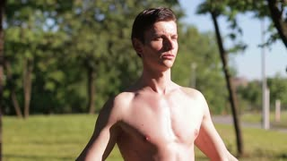 A guy posing without a T-shirt in the park