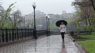 A guy walks along a lonely street under an umbrella. Front view
