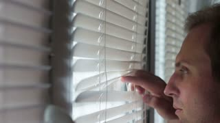 A guy with pimples on his face looking through the blinds in the window