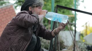 A homeless man is washing and drinking water in a dump