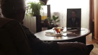A lonely old woman looking at the photo of her deceased husband. Nostalgia and loneliness