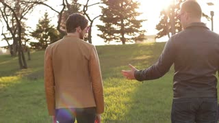 A male couple walking together in a park holding hands