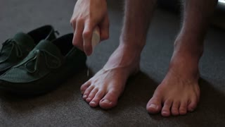 A man applying a remedy for the smell of his feet