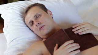 A man is sleeping with a book in his hands. Uninteresting book or fatigue