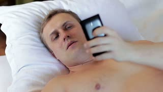 A man lying in bed and using a smartphone