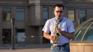 A man performing jazz compositions on a saxophone in the street