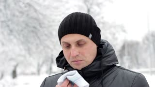 A man sick with flu or cold using a handkerchief