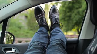 A resting driver poking his feet out of the window