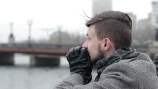 A sad young man with problems on a bridge by the river