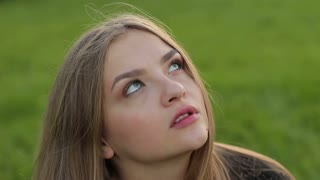 A woman looking dreamily into the sky. The innocent look of the blue eyes