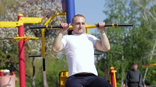 A young athlete trains in the street. Street workout