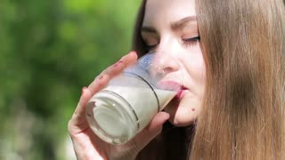 A young beautiful woman is drinking milk outdoor. Close-up