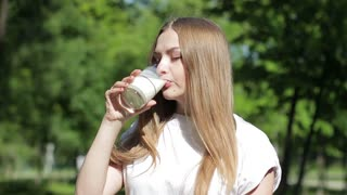 A young beautiful woman is drinking milk outdoor