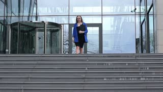 A young female employee of the firm descends the stairs of the business center