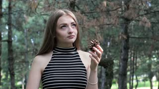 A young girl makes a wish on the background of the forest. She holds a pine cone