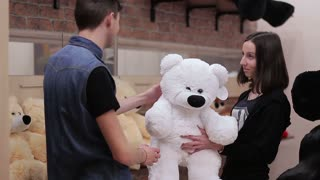 A young guy buys a stuffed toy.