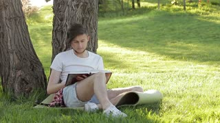 A young guy reading a book under a tree in the nature
