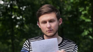 A young guy reading a letter and upset