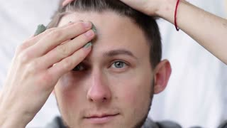A young man applying a clay mask on his face