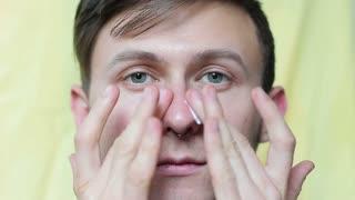 A young man applying a face cream. Men's cosmetics