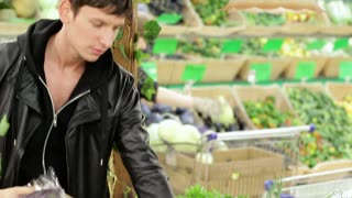 A young man choosing vegetables in a supermarket