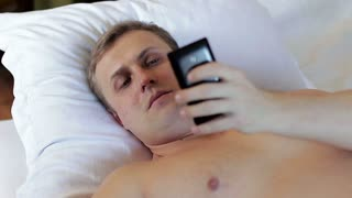A young man falling asleep in bed with a smartphone in his hands