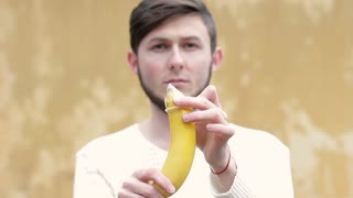 A young man putting on a condom on a banana. The concept of safe sex and prevention of sexually transmitted diseases