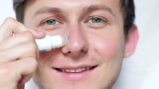 A young man using a remedy for acne and acne on his face