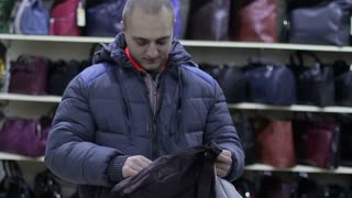 A young person buys a travel bag in a store.