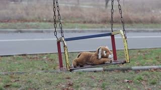 Abandoned soft toy swinging on a swing in an empty park. The concept of loss of interest and uselessness