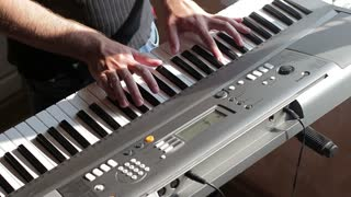 Actor playing on the keyboard synthesizer piano keys. Close-up