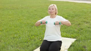 An energetic elderly woman doing exersices with dumbbells outdoors
