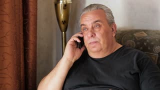 An older man talking on the phone at home