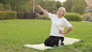 Attractive woman 60 years doing fitness, outdoors