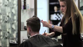 Barber cuts the hair of the young client with trimmer