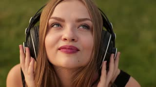 Beautiful blond girl with headphones listening to music