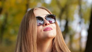Beautiful girl taking off sunglasses in an autumn park