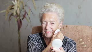 Beauty and attractiveness. Old woman doing makeup. Blush or powder