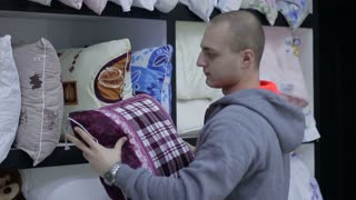 Bed linen shop. Young Man chooses plaid pillow.