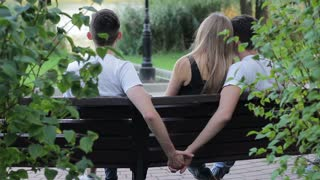 Bisexuality. A guy sitting on a bench with his girlfriend secretly holding the hand of a friend