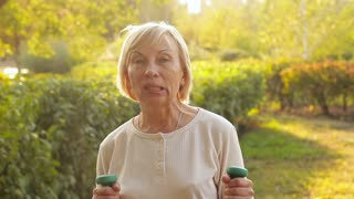 Cheerful elderly woman vigorously waves dumbbells