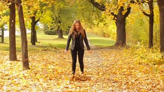 Cheerful girl throwing up leaves and having fun in the autumn park, slow motion