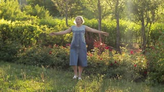 Cheerful happy elderly woman dancing and walking in the garden