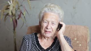 Cheerful old woman talking on the phone. She laughs and rejoices