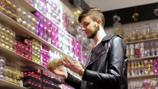 Christmas shopping. The guy is choosing the Christmas decorations. buying balls for a Christmas tree