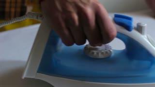 Close up of man ironing shirt